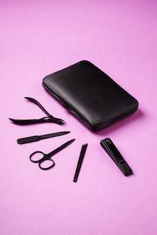 Zestaw narzędzi i akcesoriów do manicure i pedicure, blisko etui, kąt widzenia, różowe tło