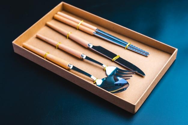 Zestaw narzędzi kuchennych z nożem, widelcem i łyżką na ciemnym tle