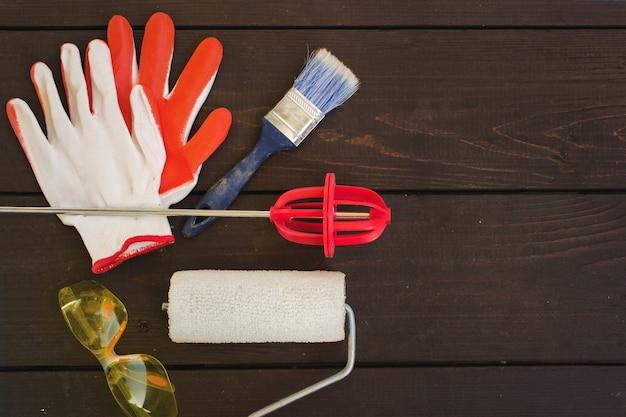 Zestaw narzędzi malarza na drewnianym tle. narzędzia malarskie do domu.