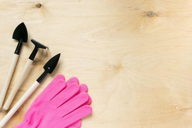Zestaw narzędzi ogrodniczych i różowe rękawiczki na podłoże drewniane. miejsce na tekst.