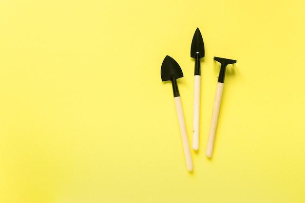Zestaw narzędzi ogrodniczych. łopaty i grabie na żółtej powierzchni, miejsca na tekst.