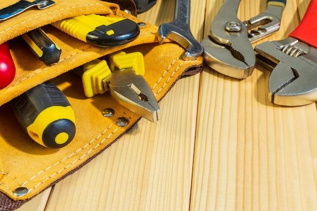 Zestaw narzędzi w torbie dla hydraulików na drewnianej ścianie