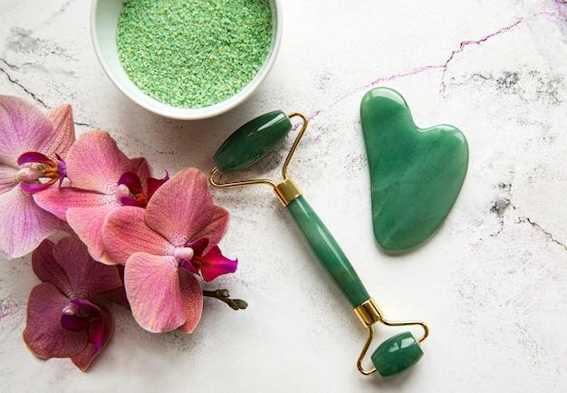 Zestaw naturalnych organicznych kosmetyków spa z kwiatami orchidei. płaska leżała sól do kąpieli, wałek do twarzy, kwiaty orchidei na tle marmuru. pielęgnacja skóry, koncepcja zabiegów kosmetycznych