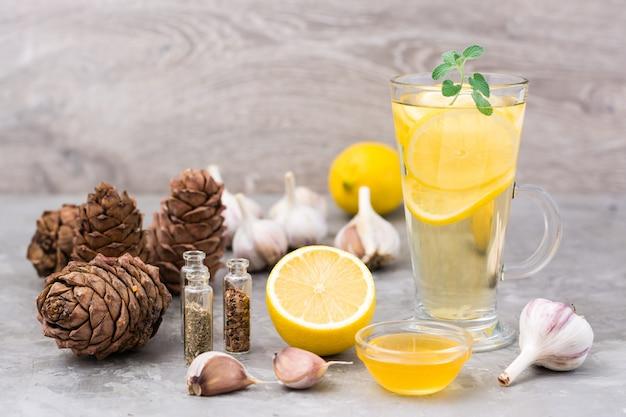 Zestaw naturalnych środków przeciwwirusowych: cytryna, czosnek, miód, zioła, żywica cedrowa na stole. medycyna alternatywna. opieka immunologiczna
