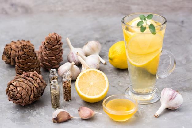 Zestaw naturalnych środków przeciwwirusowych: cytryny, czosnku, miodu, ziół, żywicy cedrowej na szarym stole