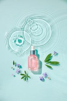 Zestaw nawilżających kosmetyków kosmetycznych na wodę z kroplami. szklana butelka serum i słoik kremu na powierzchni aqua z falami w słońcu. koncepcja reklamy organicznej nawilżającej pielęgnacji skóry, spa.