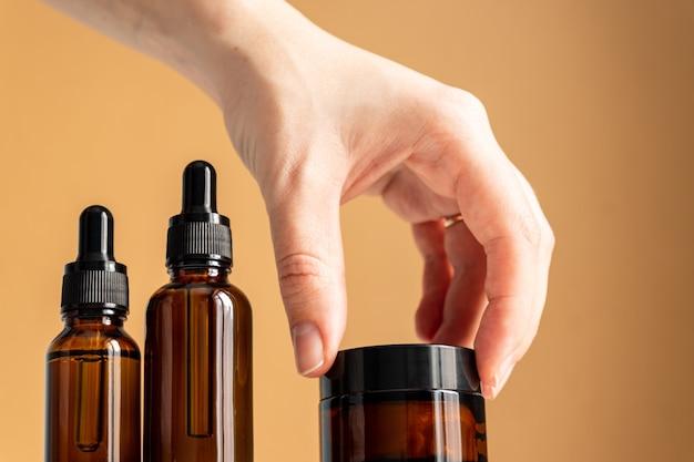 Zestaw niemarkowych kosmetyków. zakraplacze do serum z ciemnego szkła i słoiczek z kremem na beżowym tle.