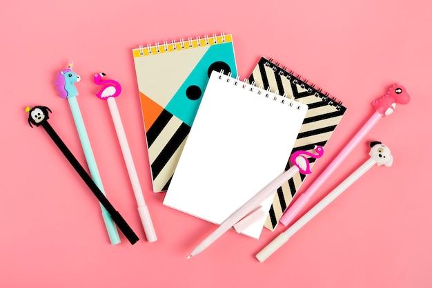 Zestaw notatników dla notatek i długopisy na różowym tle