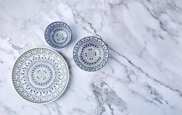 Zestaw nowoczesnych modnych niebieskich talerzy na marmurze.