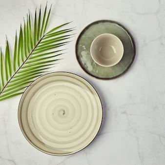 Zestaw nowoczesnych, modnych talerzy na marmurze. minimalistyczne mieszkanie leżało z zastawą stołową i tropikalnymi liśćmi