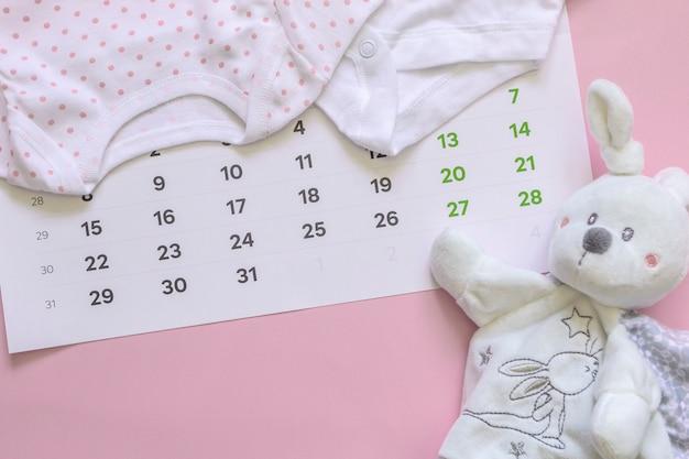 Zestaw nowonarodzonych akcesoriów w oczekiwaniu na dziecko - kalendarz, ubrania dla dzieci, zabawki.