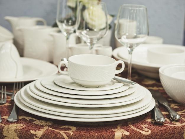 Zestaw nowych naczyń na stole z obrusem. stos białych talerzy i kieliszków do wina z kwiatami na stole restauracji. płytkie dof