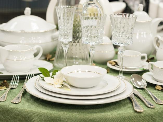 Zestaw nowych naczyń na stole z zielonym obrusem. sterta biali talerze z kwiatami na restauracja stole. płytkie dof