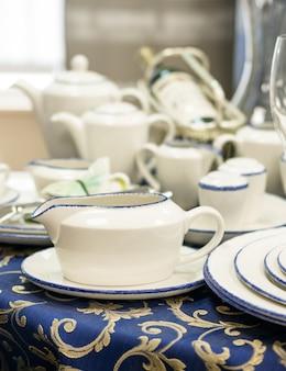 Zestaw nowych naczyń z bliska na stole z niebieskim obrusem. spodek, talerze, czajniki, butelka wina na stole. płytkie dof. pionowy