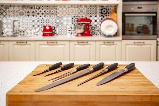 Zestaw noży kuchennych na drewnianej desce do krojenia.