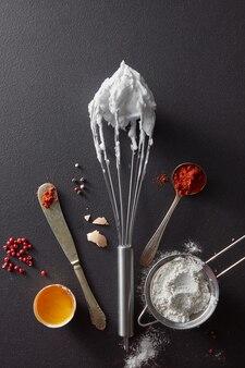 Zestaw noży z pieprzem, sitko z mąką, metalową trzepaczką i gotowanymi jajkami na czarnym betonie