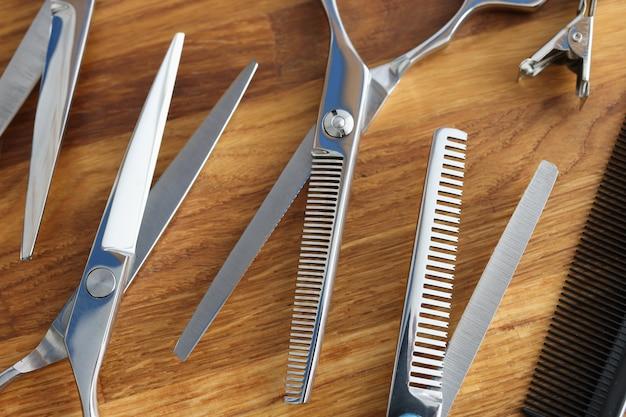 Zestaw nożyczek i grzebieni na drewnianym stole zawód fryzjera koncepcji