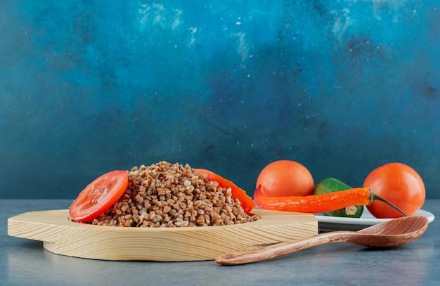 Zestaw obiadowy gotowanej gryki z plastrami pomidora obok łyżki i talerza pomidorów, ogórków i papryki na niebieskim tle. zdjęcie wysokiej jakości