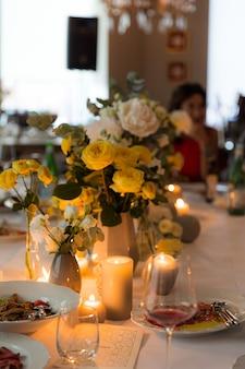 Zestaw obiadowy z żółtymi różami na uroczyste przyjęcie przy świecach
