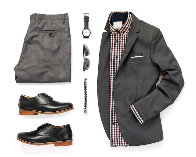 Zestaw odzieży męskiej z biurową koszulą, szarym garniturem, zegarkiem, okularami przeciwsłonecznymi, bransoletą, spodniami i czarnym butem na białym tle na białym tle, widok z góry