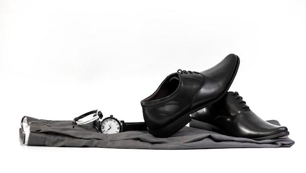 Zestaw odzieży męskiej z czarnymi butami, zegarkiem i bransoletą na białym tle