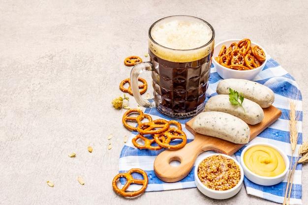 Zestaw oktoberfest. ciemne piwo, weisswurst, precle, musztarda, kłoski ziarna, chmiel