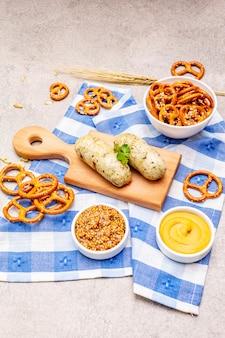Zestaw oktoberfest. weisswurst z białej kiełbasy, precle, musztarda, kłoski ziarna, chmiel