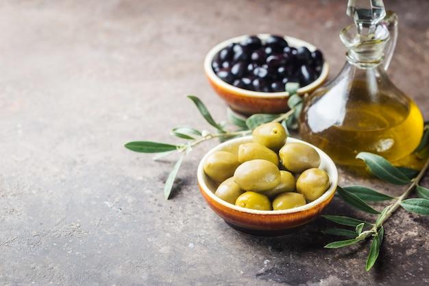 Zestaw oliwek zielonych i czarnych oraz oliwy z oliwek na ciemnym tle kamienia.