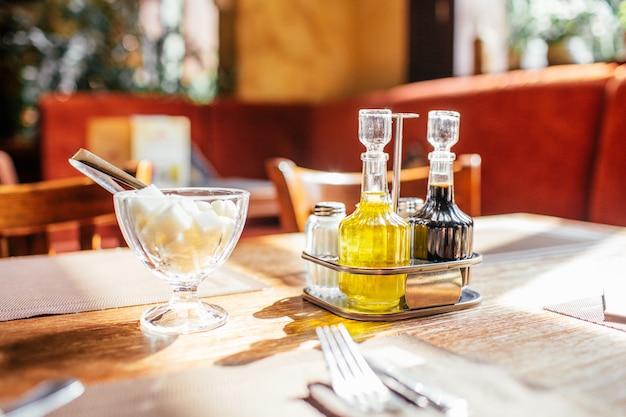 Zestaw oliwy z oliwek z sosem sojowym i cukiernicą na stole w kawiarni w promieniach słońca