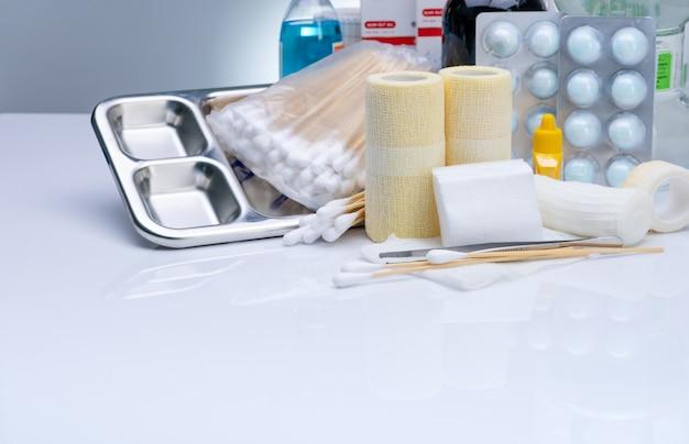 Zestaw opatrunkowy do ran i płytka ze stali nierdzewnej, kleszcze, wacik, bandaż dopasowujący, elastyczny bandaż podtrzymujący kohezję, jodopowidon, wacik z alkoholem. sprzęt medyczny dla pielęgniarki.