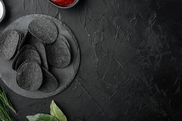 Zestaw ostrych przekąsek z serem i szczypiorkiem, na czarnym tle kamienia, widok z góry płaski, z miejscem na kopię tekstu