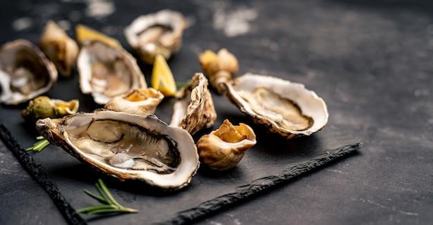 Zestaw ostryg i ślimaków na czarnym półmisku