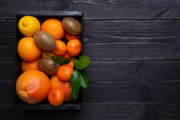 Zestaw owoców cytrusowych zwiększających odporność w czarnym pudełku na ciemnym tle. koncepcja podniesienia odporności.