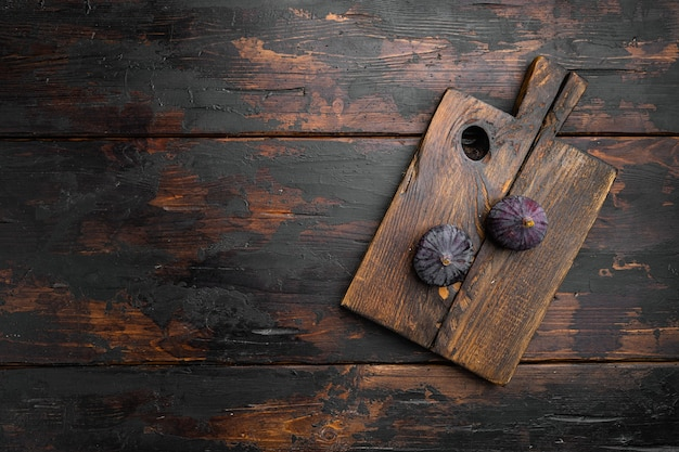 Zestaw owoców dojrzałych słodkich fig, na starym ciemnym tle drewnianego stołu, widok z góry płasko leżał, z miejscem na kopię tekstu