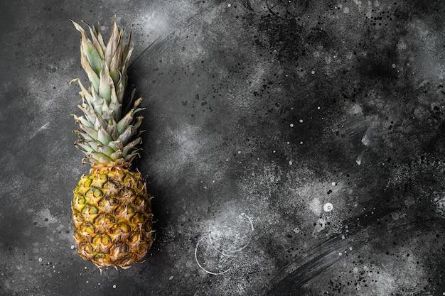 Zestaw owoców tropikalnych ananasa, na czarnym tle ciemnego kamiennego stołu, widok z góry płasko leżący, z miejscem na kopię tekstu