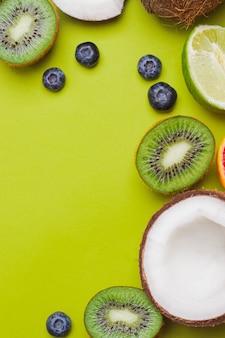 Zestaw owoców tropikalnych kiwi, krwistoczerwony, kokosowy, mango, jagodowy, limonkowy, na zielonej ścianie. owocowa rama owocowa. flatlay z copyspace. koncepcja odporności. owoce dla wzmocnienia odporności. muzyka pop