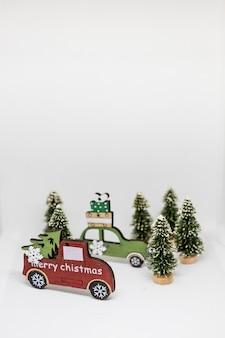 Zestaw ozdób choinkowych na białym tle. miniaturowy drewniany samochód z jodły. historia chismas. bajka, miniaturowa sceneria z miejsca kopiowania. koncepcja świąt bożego narodzenia. kreatywna pocztówka