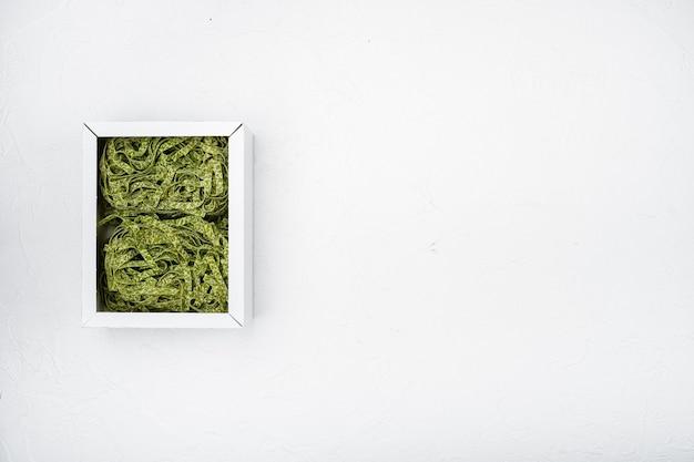 Zestaw paczek makaronu szpinakowego, na białym tle kamiennego stołu, widok z góry płasko leżący, z miejscem na kopię tekstu