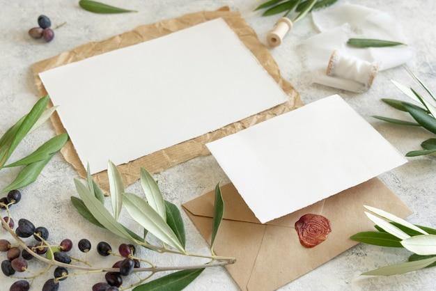 Zestaw papeterii ślubnej leżący na marmurowym stole ozdobionym gałązkami oliwnymi. elegancki nowoczesny szablon z poziomymi czystymi kartami papieru i zapieczętowaną kopertą. makieta śródziemnomorska płaska