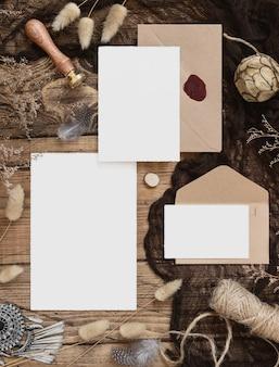 Zestaw papeterii ślubnej z kopertą leżącą na drewnianym stole z artystyczną dekoracją wokół. makieta sceny z pustymi kartkami z życzeniami i widokiem z góry suszonych roślin. kobiecy płasko leżący boho
