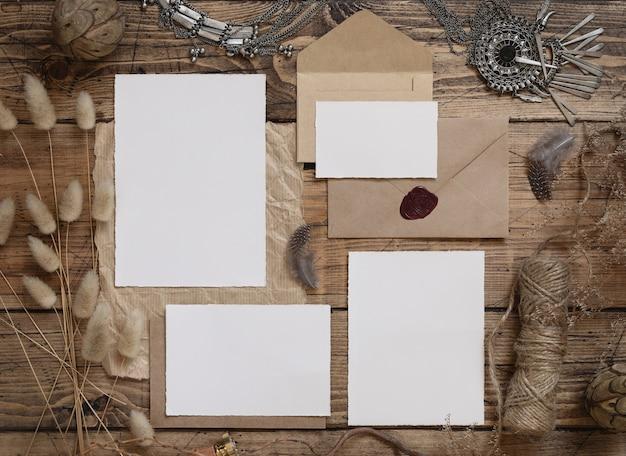Zestaw papeterii ślubnej z kopertą leżącą na drewnianym stole z artystyczną dekoracją wokół. makieta sceny z widokiem z góry kartki z życzeniami pustego papieru. kobiecy płasko leżący boho