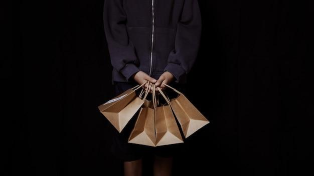 Zestaw papierowych toreb na zakupy trzymanych przez rękę osoby na czarnym tle