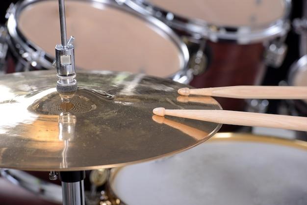 Zestaw perkusyjny i kije są na płycie.