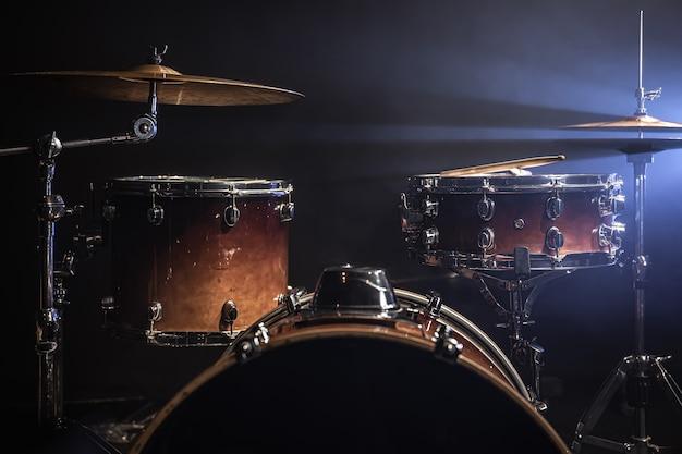 Zestaw perkusyjny na ciemnym tle z oświetleniem scenicznym, miejsce.