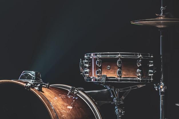 Zestaw perkusyjny w ciemnym pomieszczeniu z pięknym oświetleniem, werbel, talerze, bęben basowy.