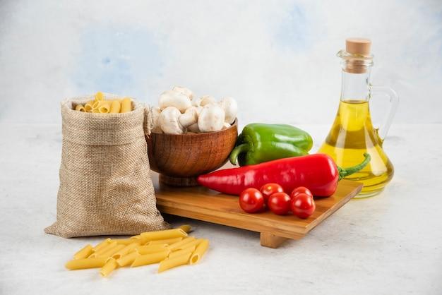 Zestaw pieczarek, oliwa extra virgin, makarony, pomidorki koktajlowe i papryczki chili na kawałku marmuru.