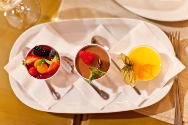 Zestaw pięknych włoskich deserów z jagodami, czekoladą, syropem z pomarańczy lub cytryny, ze skórką, czekoladą.