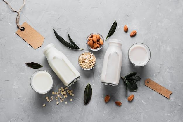 Zestaw płaskich butelek i szklanek mleka z płatkami owsianymi i migdałami