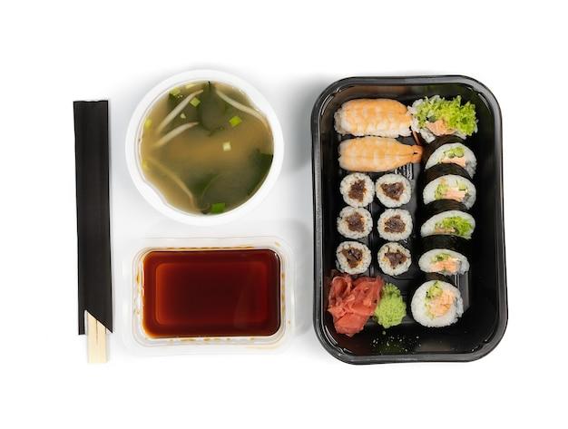 Zestaw plastikowych pojemników z zestawem sushi, sosem sojowym i zupą miso gotowy do dostawy na wynos. zabierz pudełko na lunch z rolkami susi na białym tle widok z góry