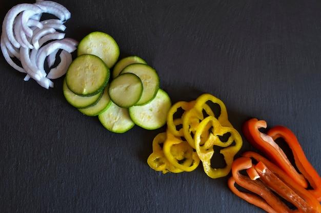 Zestaw plastrów warzyw (papryka, cebula, cukinia) na białym tle na czarnym tle. widok z góry